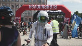 Kiev/Ukraine-June,1 2019 Men in cosmonaut costume with bike. Cyclist in white astronaut suit. Young boy with bike at cycling parad stock footage