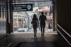 Kiev, Ukraine - June 18, 2016: Silhouettes of young couples passing through a tunnel royalty free stock photography