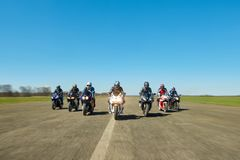 Seven bikers are riding along the field road. Kiev, Ukraine - 29 March 2017: Dynamic photo of seven bikers riding on motorcycles along the long road somewhere Royalty Free Stock Photography