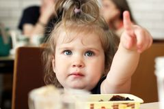 Kiev, Ukraine - March 20, 2018: A little girl is sitting at the table and showing up. Child close up royalty free stock image