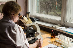 KIEV, UKRAINE, MARCN, 2017:  The laboratory assistant conducts medical examination with the help of microscope, Kiev, Ukraine. KIEV, UKRAINE, MARCN, 2017:  Close Royalty Free Stock Photo