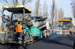 KIEV, UKRAINE, MARCN, 2017:  Road-building works with asphalt R. KIEV, UKRAINE, MARCN, 2017:  Workers laying asphalt on the roadway with an asphalt paver Royalty Free Stock Image
