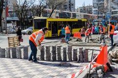KIEV, UKRAINE, MARCN, 2017:  Workers laying paving tiles, Kiev,. KIEV, UKRAINE, MARCN, 2017:  In the foreground, workers laying paving tiles in the background, a Stock Photography