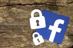 Facebook icon with locks placed on old wooden background Stock Photos