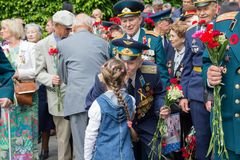 Kiev, Ukraine - May 9, 2016: Girl gives flowers to the veterans of the Great Patriotic War. In the park of eternal glory Stock Image