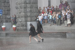 Kiev, Ukraine - May 27, 2016: Girls go without an umbrella in the pouring rain Stock Photos