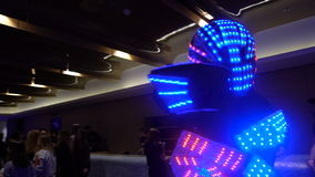 KIEV, UKRAINE - MAY 14, 2017: Glowing robot is walking in the hall with people. Events and the evening entertainment stock video