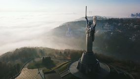 Kiev Ukraine The Motherland Monument. Aerial drone video footage of huge steel statue of woman with shield and sword. Cold foggy beautiful autumn morning in stock video footage