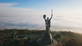 Kiev Ukraine The Motherland Monument from the back. Aerial drone video footage of huge steel statue of woman with shield. And sword. Down town from the top stock footage