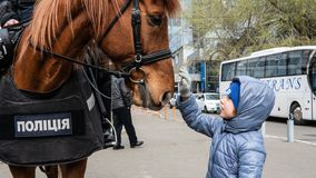 Kiev, Ukraine - 04.14.2019. Mounted police. Little boy with a horse. A crowd of Ukrainians are going to the stadium to support the royalty free stock photos