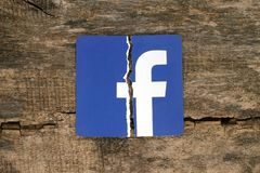 Facebook icon printed on paper, torn and put on old wooden backg stock photo