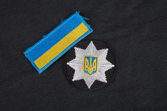 KIEV, UKRAINE - NOVEMBER 22, 2016. Patch and badge of the National Police of Ukraine on black uniform background royalty free stock images