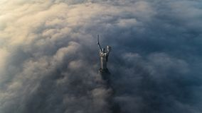 Thick clouds of autumn fog and the Motherland monument sticking out of them stock photo