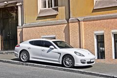 Kiev, Ukraine - November 3, 2017; White Porsche Panamera parked on the sidewalk against the backdrop of a private house stock photo