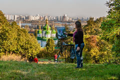 KIEV, UKRAINE - OCTOBER 11, 2014: Girl paints a picture on a bac Stock Image