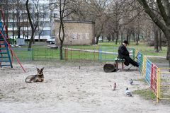 Kiev, Ukraine, 16.04.2006. An old man and a dog are on the playground of the yard. Kiev, Ukraine, 16.04.2006 An old man is reading a book and a dog is lying on stock images