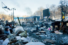 KIEV, UKRAINE: Ordinary citizens looking over barricades against the special forces on snowy destroyed street Royalty Free Stock Photos