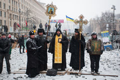 KIEV, UKRAINE: Priests of Ukrainian Orthodox Churc. H stand at front of barricades on the snow winter street during anti-government protest Euromaidan on January Stock Photo