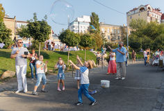 Kiev, Ukraine - Sepnember 19, 2015: Man entertains children running large bubbles Royalty Free Stock Photos