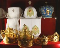 Crown and priests hats on a red background.  stock image
