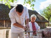 KIEV, UKRAINE - SEPTEMBER 18, 2016: man and boy making clay pot Royalty Free Stock Photography