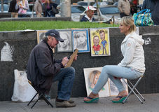 Kiev, Ukraine - September 14, 2015: Street artist paints a portrait of a young woman Royalty Free Stock Photos