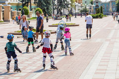 Kiev, Ukraine the 8th of July - A group of children in sport equipment with instructor doing rollerskating exercises in Mariinsky Royalty Free Stock Images