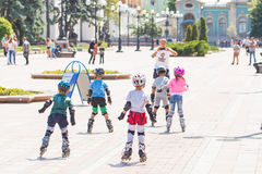 Kiev, Ukraine the 8th of July - A group of children in sport equipment with instructor doing rollerskating exercises in Mariinsky Stock Photo