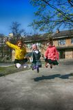 Kiev. Ukraine. 15.04.2010 Three schoolgirls are in jump on the street on a spring day royalty free stock photos
