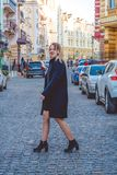 Kiev, Ukraine. 30.03.2019. The young girl in black clothes in spring sunny day walks on old city streets. Dress, jacket and coat. royalty free stock image