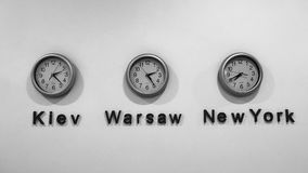 KIEV - WARSAW - NEW YORK clocks sit on a white wall in Kiev. The three clocks of an office in Ukraine show two Eastern European capitals and New York City stock photos