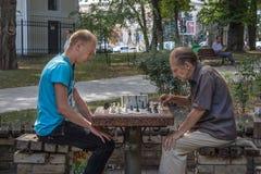 KIEW, UKRAINE - 17. AUGUST 2015: Alte und junge Männer, die Schach in Taras Shevchenko Park, Kiew, Hauptstadt von Ukraine spielen Stockfotos