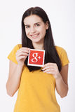 Kiew, Ukraine - 22. August 2016: Frau übergibt das Halten von Google plus die Ikone, die auf Papier auf grauem Hintergrund gedruc Lizenzfreies Stockbild