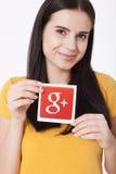 Kiew, Ukraine - 22. August 2016: Frau übergibt das Halten von Google plus die Ikone, die auf Papier auf grauem Hintergrund gedruc Lizenzfreie Stockbilder