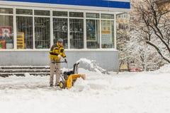 KIEW, UKRAINE - 18. DEZEMBER 2017: Arbeitskraft säubert Bürgersteig mit Schneepflugmaschine nach schweren Schneefällen Lizenzfreie Stockbilder