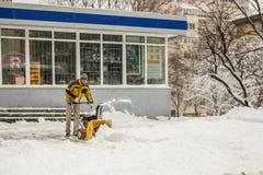 KIEW, UKRAINE - 18. DEZEMBER 2017: Arbeitskraft säubert Bürgersteig mit Schneepflugmaschine nach schweren Schneefällen Lizenzfreie Stockfotos