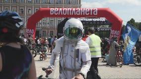 Kiew/Ukraine-Juni, 1 2019 Männer im Kosmonautkostüm mit Fahrrad Radfahrer in der weißen Astronautenklage Junge mit Fahrrad an Rad stock footage