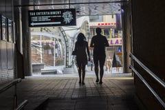 Kiew, Ukraine - 18. Juni 2016: Schattenbilder von den jungen Paaren, die durch einen Tunnel überschreiten lizenzfreie stockfotografie