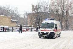 Kiew, Ukraine - 1. März 2018 Schwere Schneefälle, Frost und Blizzard in Osteuropa Autos auf Asphalt Krankenwagen, der sich beeilt Stockfotografie