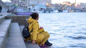 Kiew Ukraine 22-12-2018 zwei junge Mädchen in den gelben Jacken sitzen auf dem Pier stock video footage