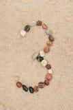 Kiezelsteen 3 aantal op zand selectieve nadruk Stock Foto