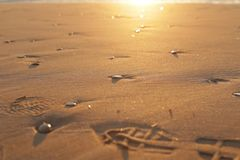 Kiezelsteenstenen en voetstappen op zand, zonsopgang stock afbeelding