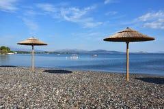 Kiezelsteenstrand en parasols in Griekenland stock foto's