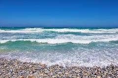Kiezelsteenstrand met oceaan Stock Afbeeldingen
