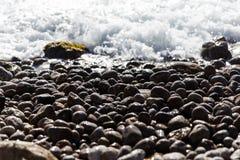Kiezelsteenstrand met schuimende golven stock foto