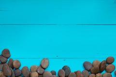 Kiezelstenen aan de kant over een geweven geschilderde blauwe achtergrond Stock Foto's