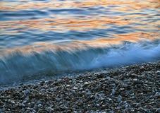 Kiezelstenen en de golven bij zonsondergang Royalty-vrije Stock Afbeelding