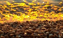 Kiezelstenen en overzees bij zonsondergang Royalty-vrije Stock Foto's