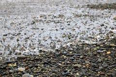 Kiezelstenen op een zandig strand, glanzende natte stenen en golven stock foto's