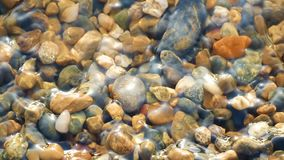 Kiezelstenen op het strand in water in langzame motie, close-up wordt gewassen dat stock footage